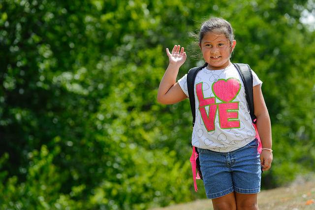 Young girl waving to someone as she walks to school