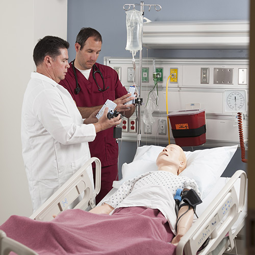 Two healthcare workers learning with a simulated patient