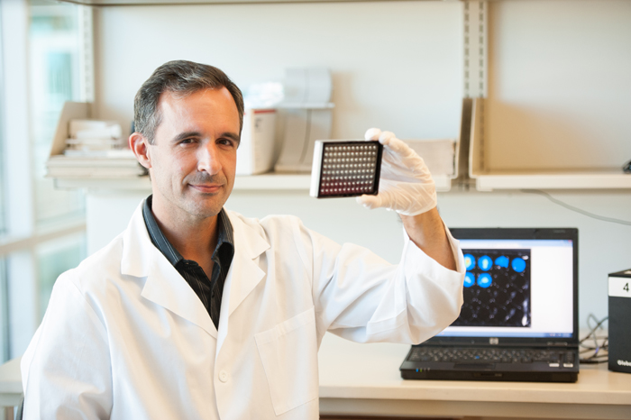 Dr. Jeffrey Cirillo poses with a sample tray in front of a laptop and, at the edge of the photograph, a prototype of the new testing device that could revolutionize TB testing.