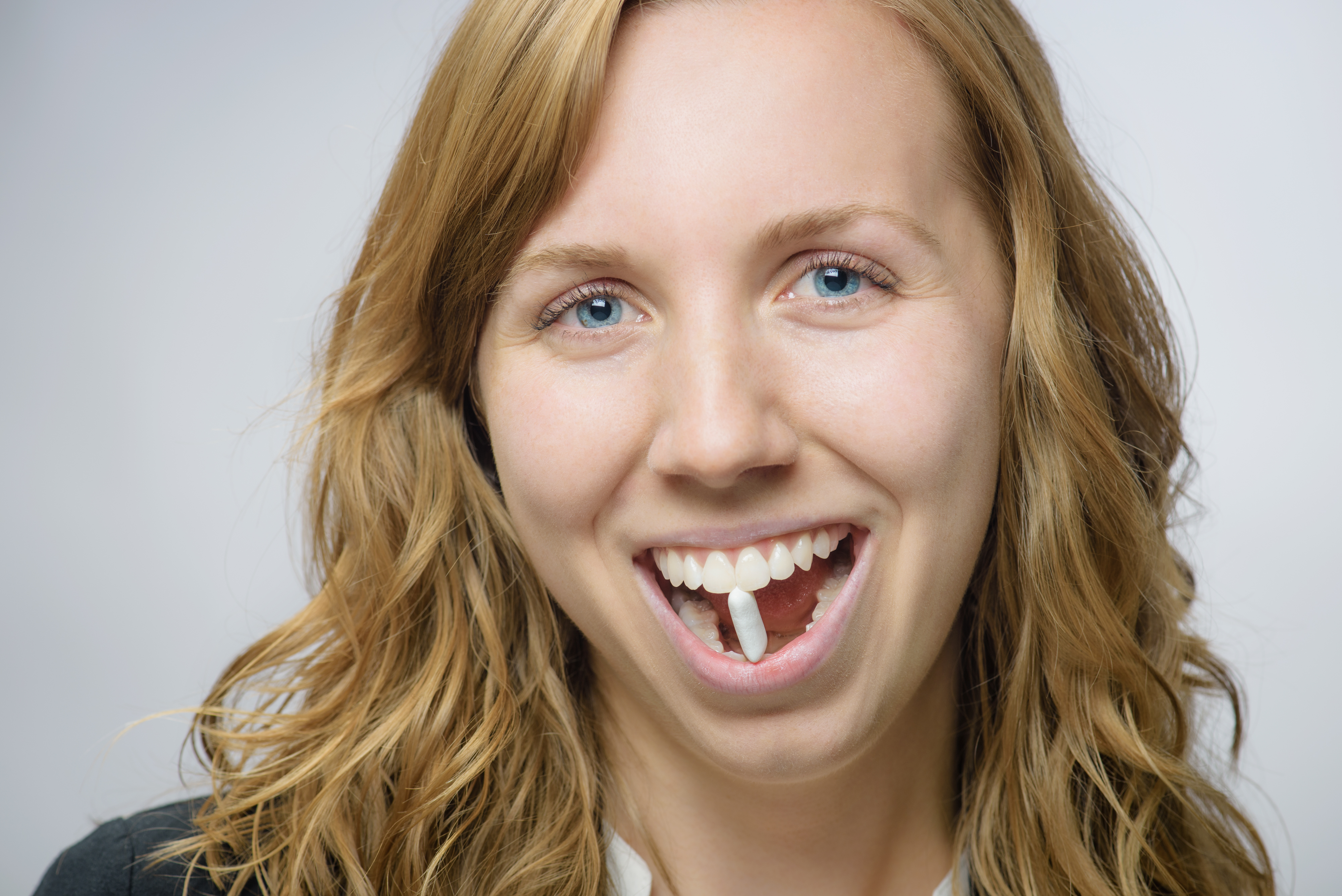 Woman smiling playfully holding a piece of gum between her teeth.