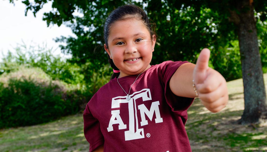 Girl giving gig'em sign