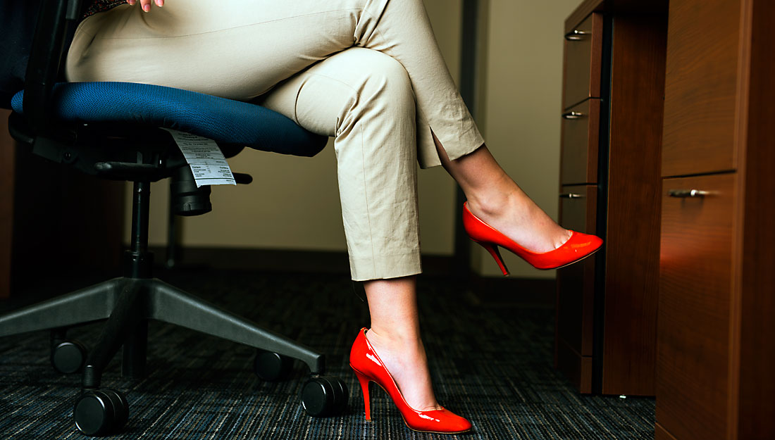 Woman at desk in bright orange high heels.