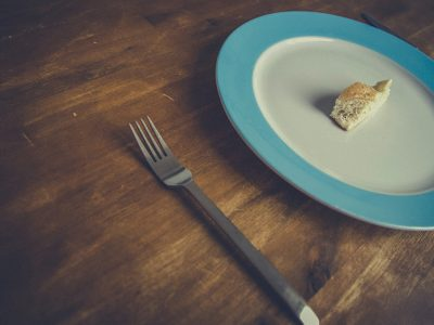 An unusually small piece of bread sits on a plate.