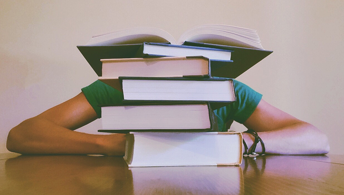 Finals Week: How to use caffeine, sleep and snacks. A person who is studying has their head on the table behind a pile of books.