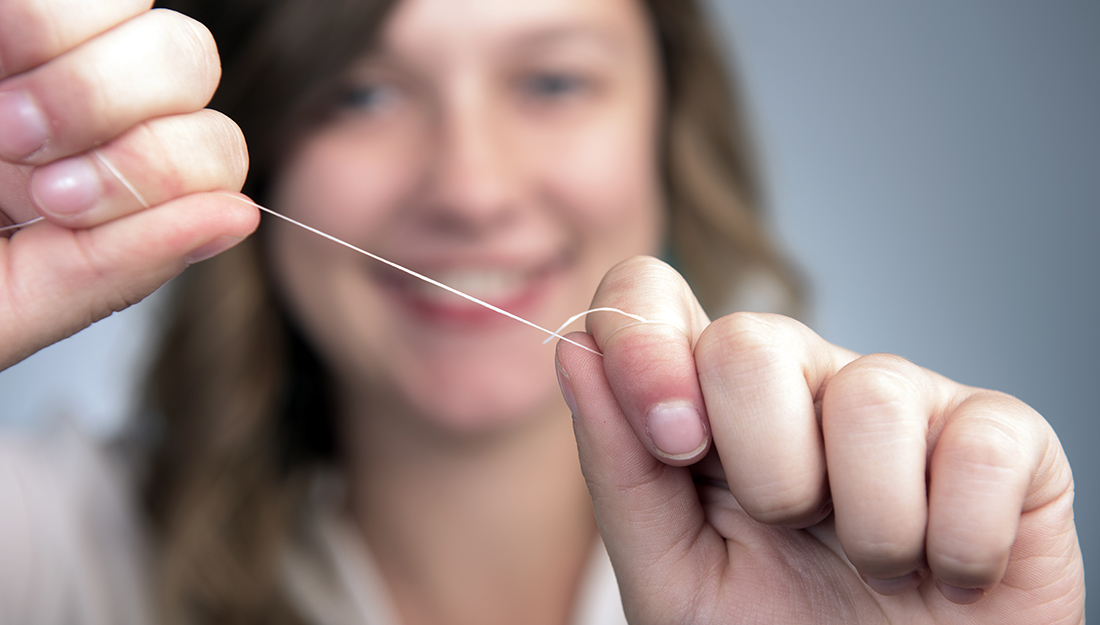 How to properly floss. A young women holds floss in her hands.
