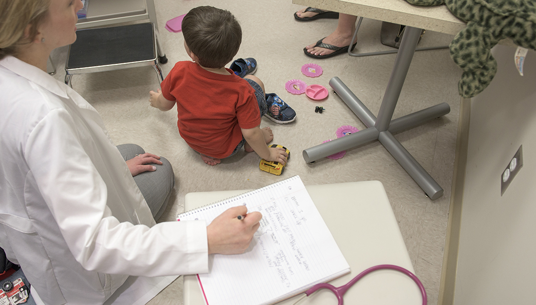 3 signs of mental illness in children-a young boy sitting on the ground playing with toys while a physician watches and takes notes