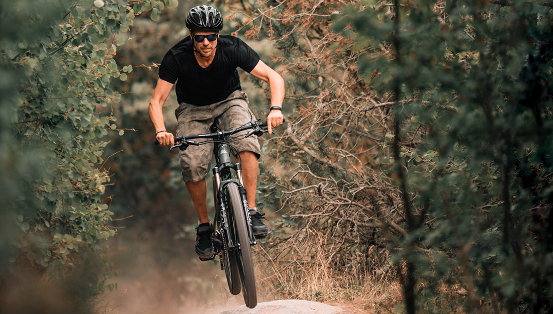 Top 5 injuries and illnesses of the summer-biking-a man is riding a bike through the trees