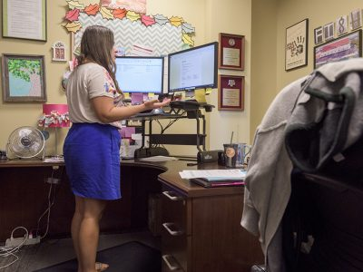 Living learning laboratory-A woman stands at her sit-stand desk in her office and works