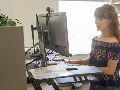 Sedentary lifestyles_A woman in using a sit-stand desk in her office on the Texas A&M campus