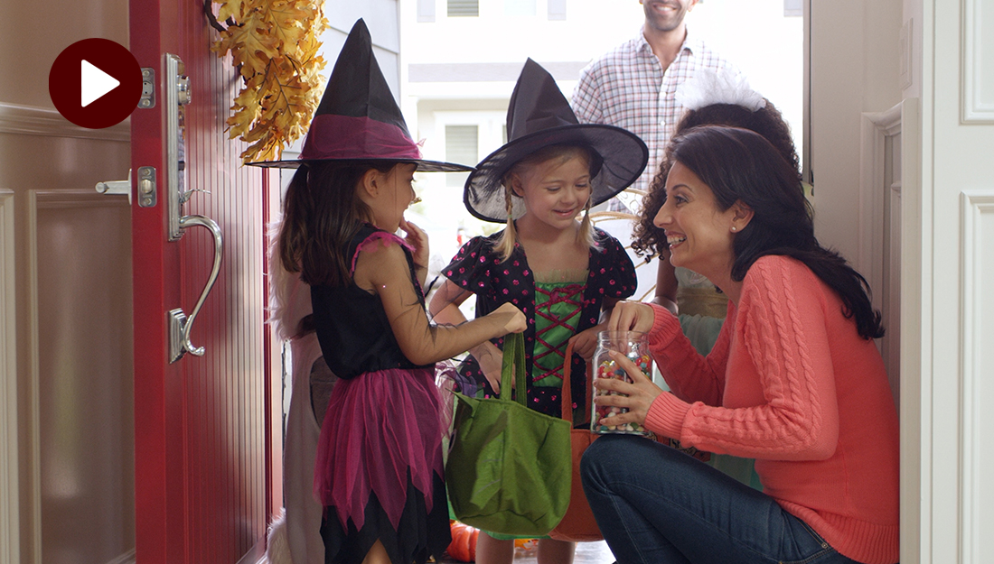 A woman is giving candy to two children dressed as witches