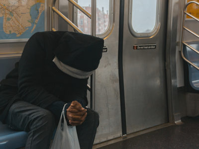 A man sitting on a bus hunched over to represent Chronic pain