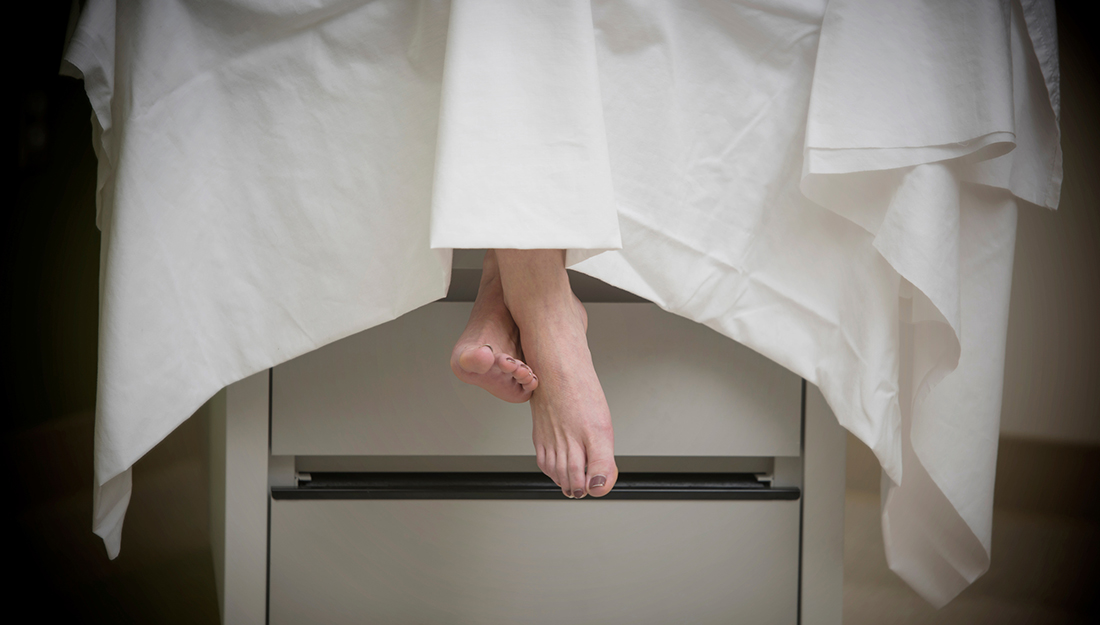 Woman's crossed feet dangling from an examination table