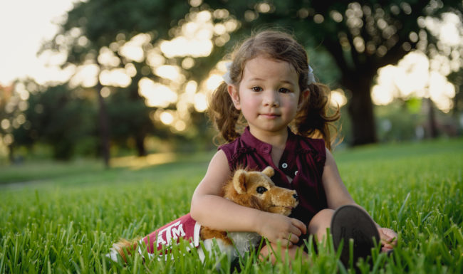 Childhood development_Child development_A young girl is sitting in grass holding a stuffed animal