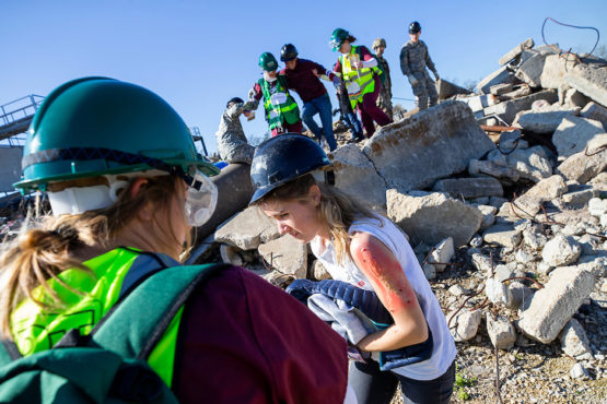 health students assist mock patients from rubble