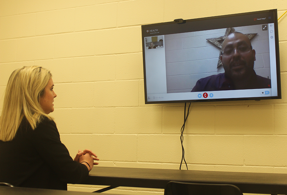 Washington County Jail_A woman sits at a table and speaks to a man on a television