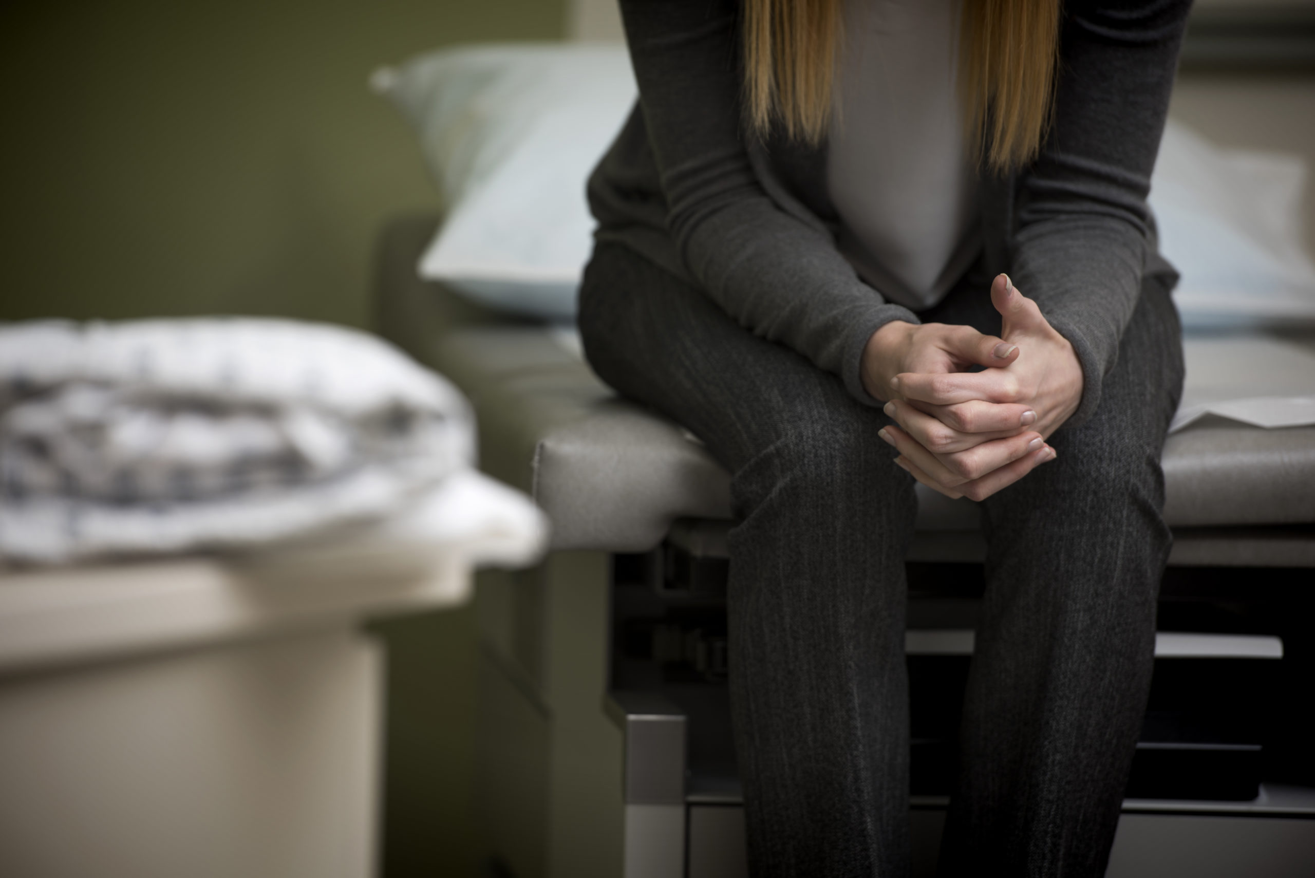 Retrovirus_Autoimmune disease_Women's health_A women is sitting on an exam table with her hangs resting on her legs