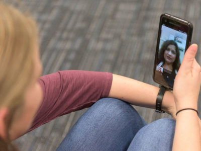 woman holding phone, talking with doctor over telemedicine