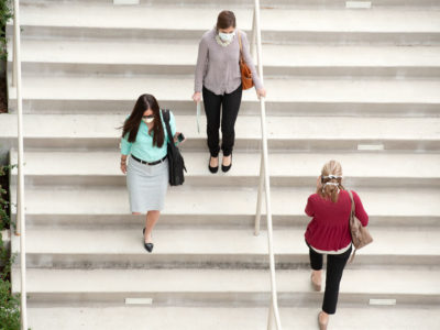 Three women walk on staircase, each wearing a surgical mask.