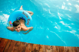 boy floating in pool with water ring