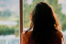 woman with dark hair looking out a window