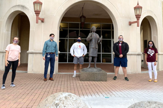five students pose in front of Rangel College of Pharmacy building wearing hand-sewn face masks