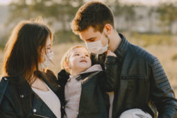 family of three wearing face coverings outdoors