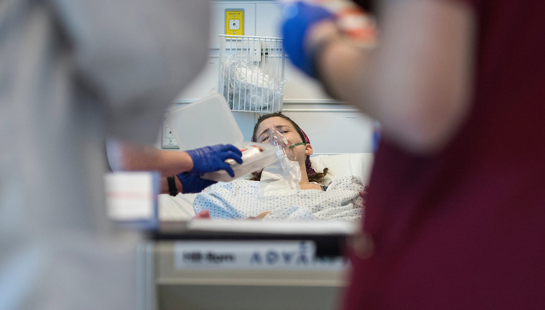 person in hospital bed receiving medical intervention