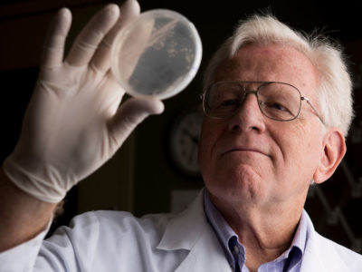 Dr. James Samuel holds up a petri dish to take a close look at pathogens