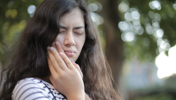 A woman with long brown hair clenches her jaw with eyes closed as if in pain