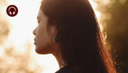 Backlit side view of woman with dark hair standing outside with eyes closed during sunset