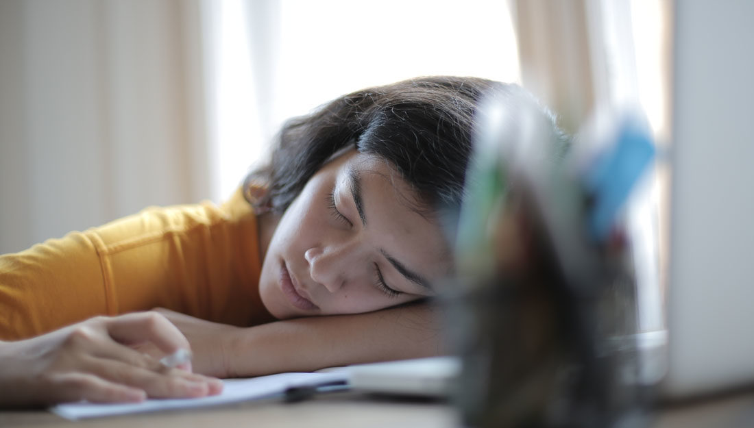 woman in yellow shirt sleeps at desk with her head resting on her arms