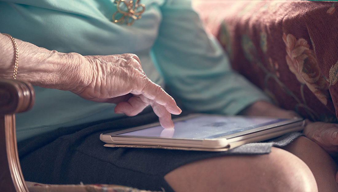 older woman reading on a tablet