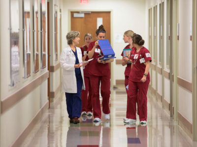 photo of nursing students in scrubs walking down a hallway with a professor in a white coat
