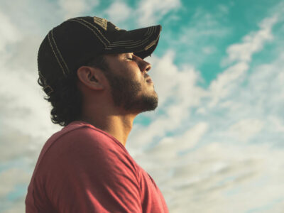 man stands outdoors with head looking up toward the sky and eyes closed