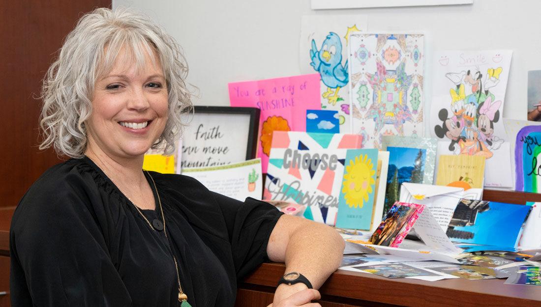 Executive Director Leigh Ann Wyatt stands beside handmade student pen-pal projects