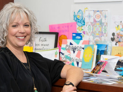 Executive Director Leigh Ann Wyatt stands beside handmade student pen-pal projects