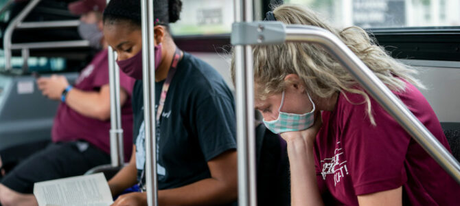 college students wearing masks ride bus