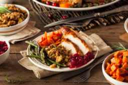 table full of Thanksgiving food, plate of turkey, stuffing, sweet potatoes, asparagus and cranberry sauce