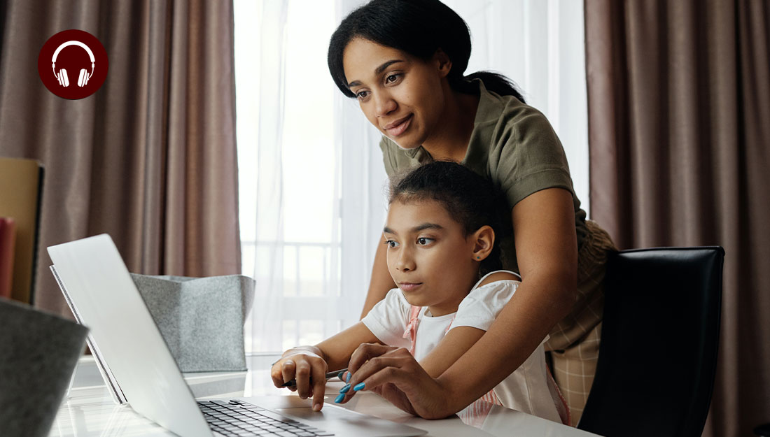 mother assists daughter with computer work at kitchen table