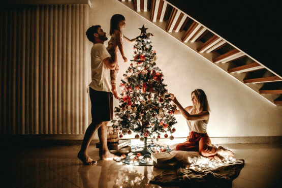 family of three decorates a Christmas tree in their home