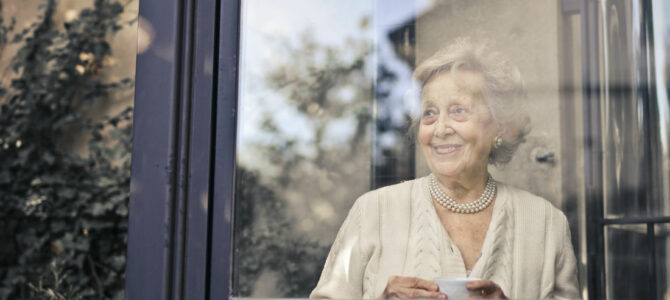 older woman stands in front of a window, smiling and holding a cup of tea or coffee
