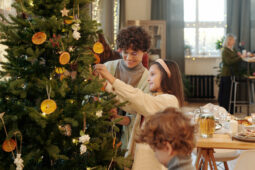 A family decorates a Christmas tree together