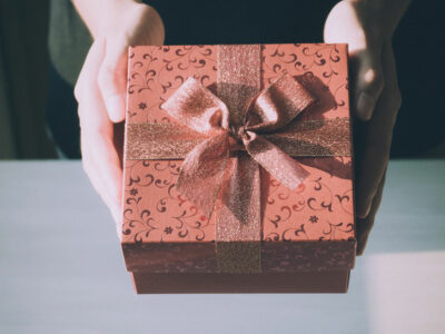 hands hold out a gift-wrapped box