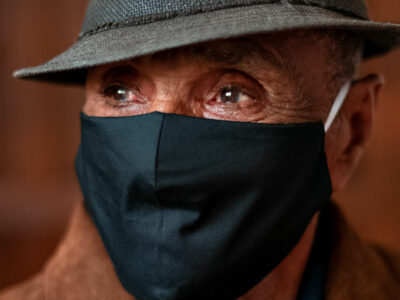 older man wearing a hat and face covering