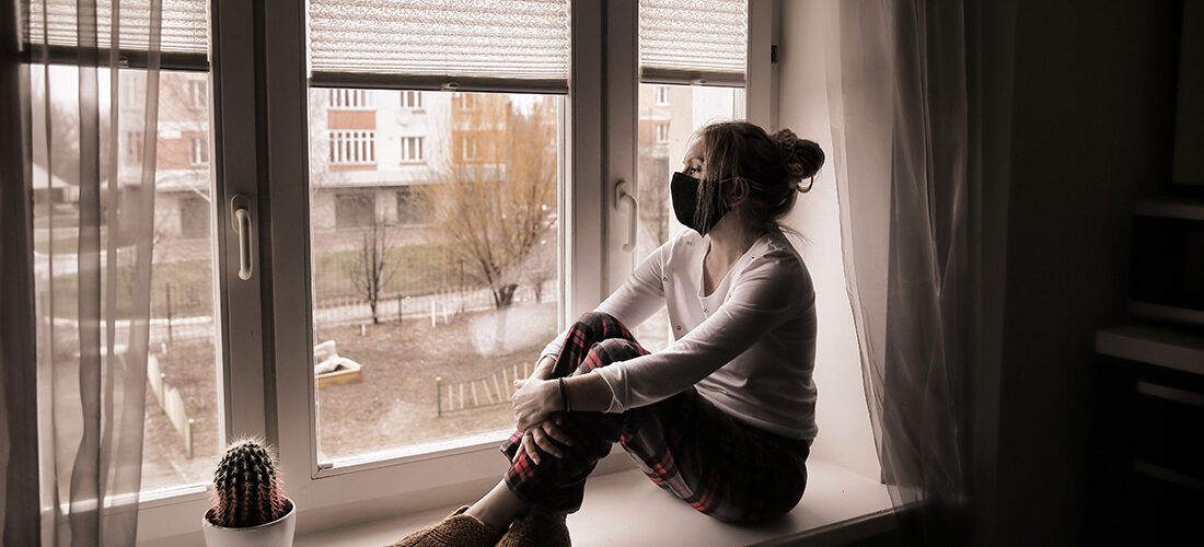А young woman in a protective mask sits on the window sill. Du
