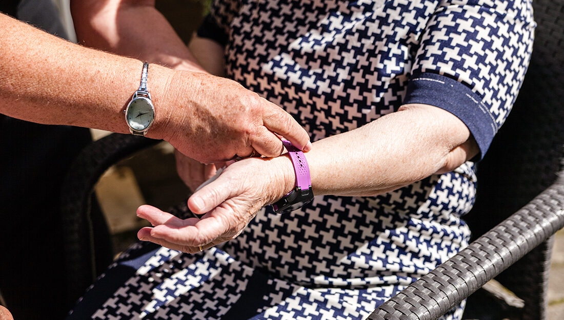 old womans is having wearable device smart watch in care home retirement house.