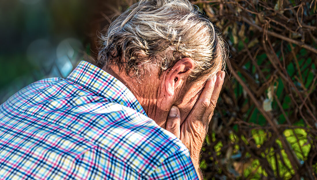 Older man worried and hiding his face in his hands. Headache. Ad