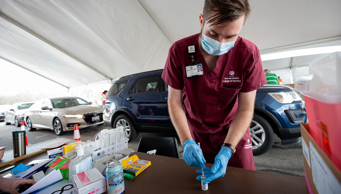a nursing student loads a syringe with the Moderna COVID-19 vaccine at a drive-through vaccine clinic in Bryan-College Station
