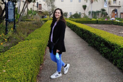 Lacy Failla stands on a hedge-lined sidewalk in a park