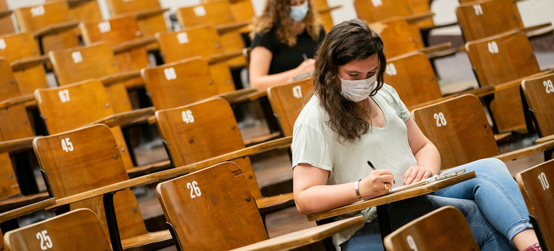 Students wearing masks sit in a lecture hall